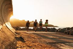 Bild in voller Länge von vier Sportleuten, die sich vorbereiten zu laufen Stockbilder