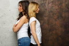 Bild von Brunette und von blonder Stellung mit ihren Rückseiten miteinander Stockbild