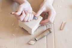 Bild von den Händen, die schnitzend auf Holz durchführen Lizenzfreies Stockfoto