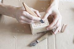 Bild von den Händen, die schnitzend auf Holz durchführen Lizenzfreie Stockfotografie