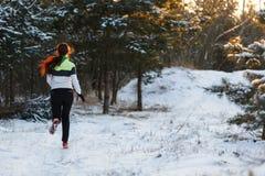 Bild von der Rückseite des Athleten in den Turnschuhen auf Morgen laufen gegen Hintergrund von Bäumen im Winter Lizenzfreie Stockbilder