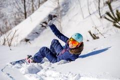 Bild von der Rückseite des Athleten im Sturzhelm, der auf schneebedeckter Steigung liegt Lizenzfreies Stockbild