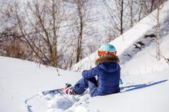 Bild von der Rückseite des Athleten im Sturzhelm, der auf schneebedeckter Steigung sitzt Stockfotos