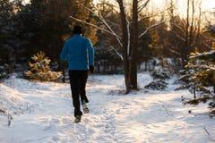 Bild von der Rückseite des jungen Athleten laufend durch Winterwald Stockfoto