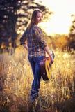 Bild von der Rückseite einer attraktiven jungen Frau auf dem karierten Hemd mit einer Akustikgitarre Lizenzfreie Stockfotos