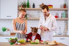 Bild von Eltern mit der Tochter, die Lebensmittel in der Küche kocht Stockfotos