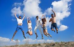 Bild von fünf Energieleuten, die am Strand springen stockfotografie