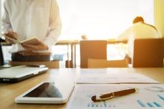 Bild von Geschäftsunterlagen auf Arbeitsplatz mit zwei Partnern Inter- Stockfotografie