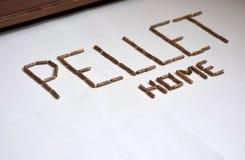 Bild von hölzernen Kugelbrennstoffkörnern auf weißen Hintergrundformungsbuchstaben und -haus Stockfoto