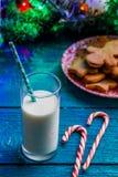 Bild von Ingwerkeksen, Glas Milch, Karamell haftet, Fichtenzweige mit brennender Girlande Stockbild