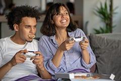 Bild von jungen liebevollen Paaren in der Küche zu Hause zuhause Pizza und das Spielen von Spielen mit Konsole essen stockbild