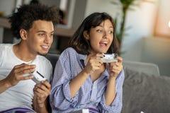 Bild von jungen liebevollen Paaren in der Küche zu Hause zuhause Pizza und das Spielen von Spielen mit Konsole essen lizenzfreie stockbilder