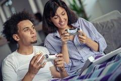 Bild von jungen liebevollen Paaren in der Küche zu Hause zuhause Pizza und das Spielen von Spielen mit Konsole essen stockfotos