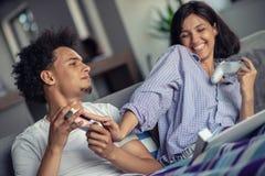 Bild von jungen liebevollen Paaren in der Küche zu Hause zuhause Pizza und das Spielen von Spielen mit Konsole essen lizenzfreies stockbild