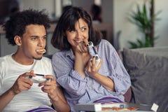 Bild von jungen liebevollen Paaren in der Küche zu Hause zuhause Pizza und das Spielen von Spielen mit Konsole essen stockbilder