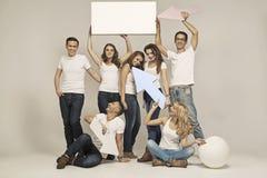 Bild von lächelnden jungen Leuten mit Zeichen lizenzfreie stockbilder