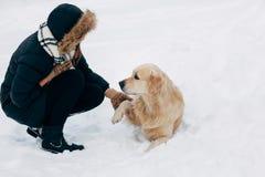 Bild von Labrador Tatze gebend dem Mädchen im Winterpark Lizenzfreie Stockbilder