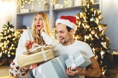 Bild von netten Paaren in Sankt-Kappe mit Geschenk im Kasten Stockbild