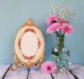 Bild von rosa und weißen Blumen und von antikem Rahmen auf Holztisch Stockfotos