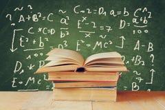 Bild von Schulbüchern auf hölzernem Schreibtisch über grünem Hintergrund mit Formeln getrennte alte Bücher Lizenzfreie Stockfotos