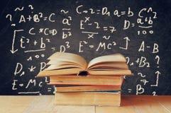 Bild von Schulbüchern auf hölzernem Schreibtisch über schwarzem Hintergrund mit Formeln getrennte alte Bücher Stockbild