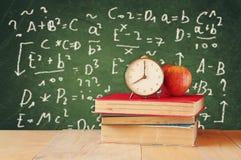 Bild von Schulbüchern auf hölzernem Schreibtisch, Apfel und Weinlese stoppen über grünem Hintergrund mit Formeln ab getrennte alt Lizenzfreies Stockbild