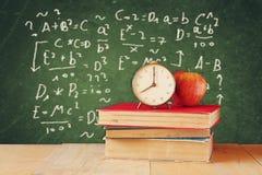 Bild von Schulbüchern auf hölzernem Schreibtisch, Apfel und Weinlese stoppen über grünem Hintergrund mit Formeln ab getrennte alt Lizenzfreies Stockfoto
