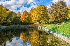 Bild von a-Teich in einem Herbstpark, der gelbe Bäume reflektiert Stockfotografie