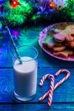 Bild von Weihnachtsplätzchen, Glas Milch, Karamell haftet, Fichtenzweige mit brennender Girlande Lizenzfreies Stockbild