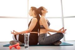 Bild von zwei jungen Frauen, die zurück zu Rückseite in fintess Raum sitzen Sie meditieren mit geschlossenen Augen Modelle sitzen stockfoto