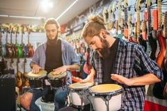 Bild von zwei jungen Männern, die Schlag auf Trommeln sitzen und haben Sie sind im Raum, der von den E-Gitarren voll ist Kerle sp lizenzfreies stockbild