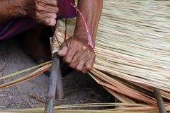Bild zeigt, wie man ein Plattenkuskusgras für Hüttendach, Handarbeithandwerk des Plattenkuskusgrases für Hüttendach, Strohdachhüt Lizenzfreie Stockfotos