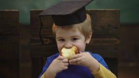 Bildad skolaungestudent med avläggande av examen och äpplet tillbaka begreppsskola till Skolbarnpojke i klassrum Rolig unge lager videofilmer