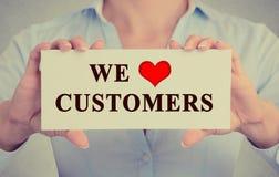 Bildaffärskvinnan räcker det hållande tecknet med meddelandet som vi älskar kunder Arkivbild