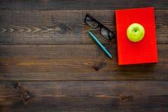 Bildande litteratur Skola läroboken, boken, orubbligt, äpplet och exponeringsglas på mörkt träutrymme för kopia för bästa sikt fö royaltyfria foton