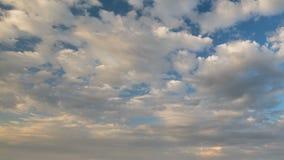 Bildande och forsrörelse av vita moln av olika former i den blåa himlen i sen vår på solnedgången arkivfilmer