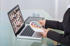 Bildeditor unter Verwendung des Laptops am Schreibtisch Lizenzfreie Stockfotografie