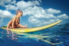 Bilden av att surfa behandla som ett barn vågor arkivfoton