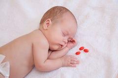 Bilden av behandla som ett barn att sova på filten med tre preventivpillerar Fotografering för Bildbyråer