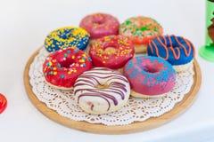 Bilden av blandade donuts i en ask med glaserad choklad, rosa färg glasade och strilar donuts Arkivfoto