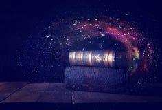bilden av bunten av antikviteten bokar över trätabell- och mörkerbakgrund fotografering för bildbyråer