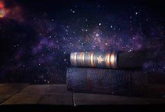 bilden av bunten av antikviteten bokar över trätabell- och mörkerbakgrund arkivbild