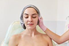 Bilden av den ansiktslösa cosmetologisten i rosa medicinska handskar på arbete i cosmetologysalong undersöker den attraktiva kvin arkivfoto