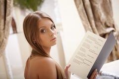 Bilden av den charmiga unga damen läser menyn arkivfoton