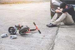 Bilden av den chockade och f?rskr?ckta chauff?ren efter olycka g?llde unges cykel och hj?lm som ligger p? v?gen p? ?verg?ngsst?ll royaltyfri fotografi