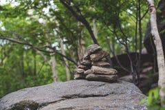 Bilden av den etniska negro spiritual stenar pyramiden i den mystiska skogen på den Sakhalin ön royaltyfri foto