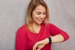 Bilden av den gladlynta blonda kvinnan ser positivt på armbandsuret, kontrollerar tid, jublar ha extra- tid, innan den möter som  arkivbild