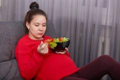 Bilden av den gravida damen för den förtjusande brunetten tycker om att äta ny sallad, har bra aptit och att vara i modern lä royaltyfri bild