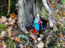 Bilden av den lilla heliga Mary statyn, satte in i en gammal stam för att tillbe arkivfoton