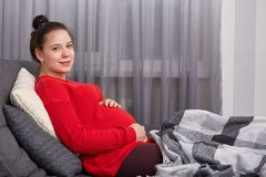Bilden av den lugna gravida kvinnlign bär den röda tröjan, håller händer på magen, ser kameran, drömmar för behandla som ett barn royaltyfri bild